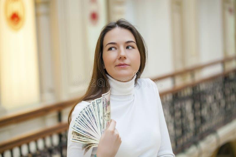 Brunetki trzyma i pokazuje żeńscy dolary zdjęcie royalty free