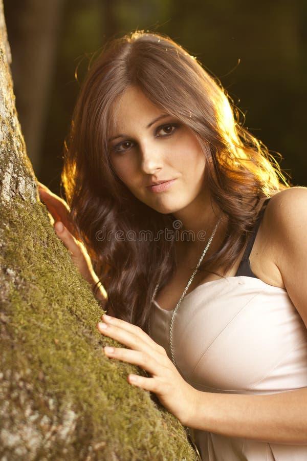 Brunetmädchen in einem magischen Wald auf Moos lizenzfreie stockbilder