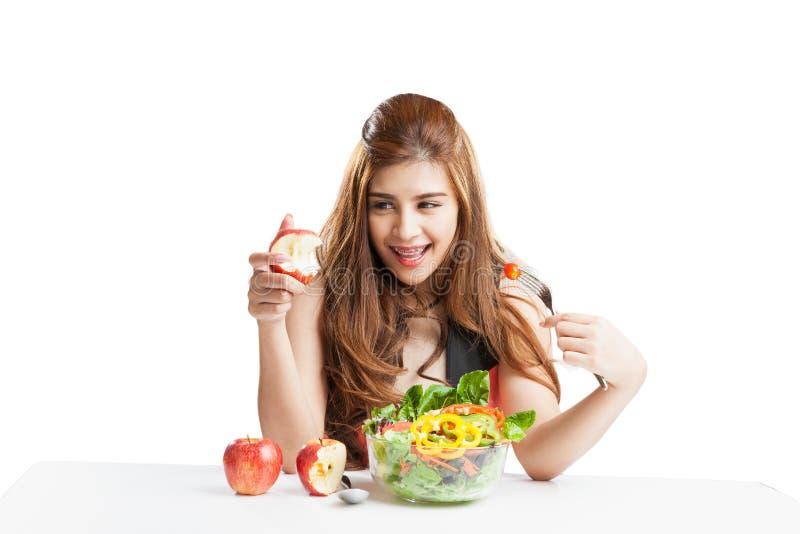 Brunett för ung kvinna som är närvarande och äter sallad royaltyfria foton