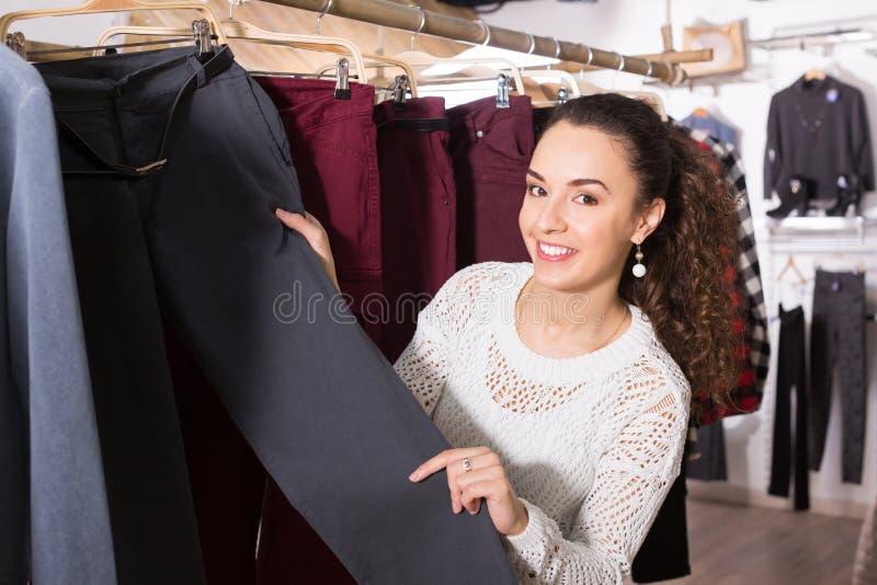 Brunett för vuxen kvinnlig som väljer ny byxa arkivfoton