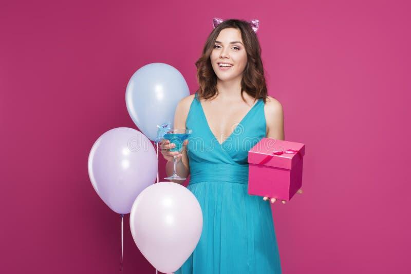 Brunett i en blå klänning som rymmer en coctail i hennes händer och en gåvaask som omges av ballonger arkivbilder