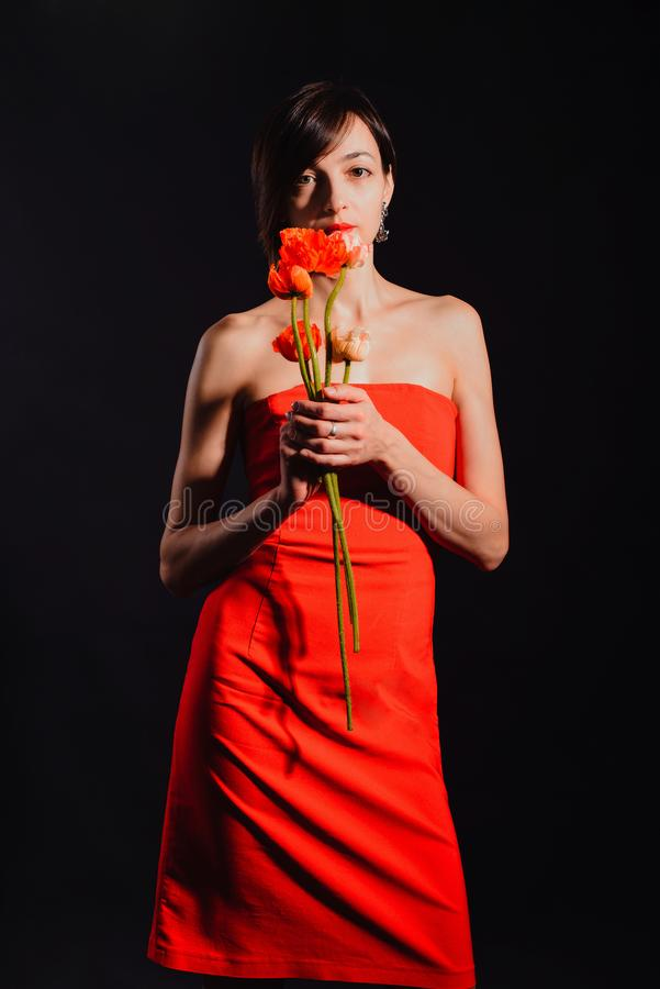 Brunett i en röd klänning med blommor på en svart bakgrund royaltyfri fotografi