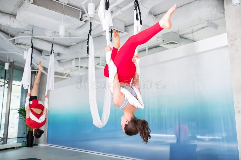Brunett i röd damasker som öva flyg- yoga fotografering för bildbyråer