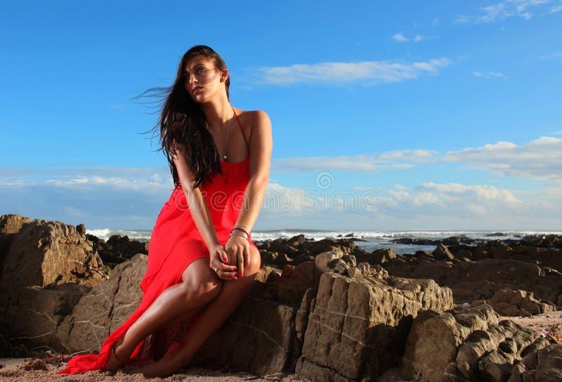 Brunett i röd klänning på stranden royaltyfri bild