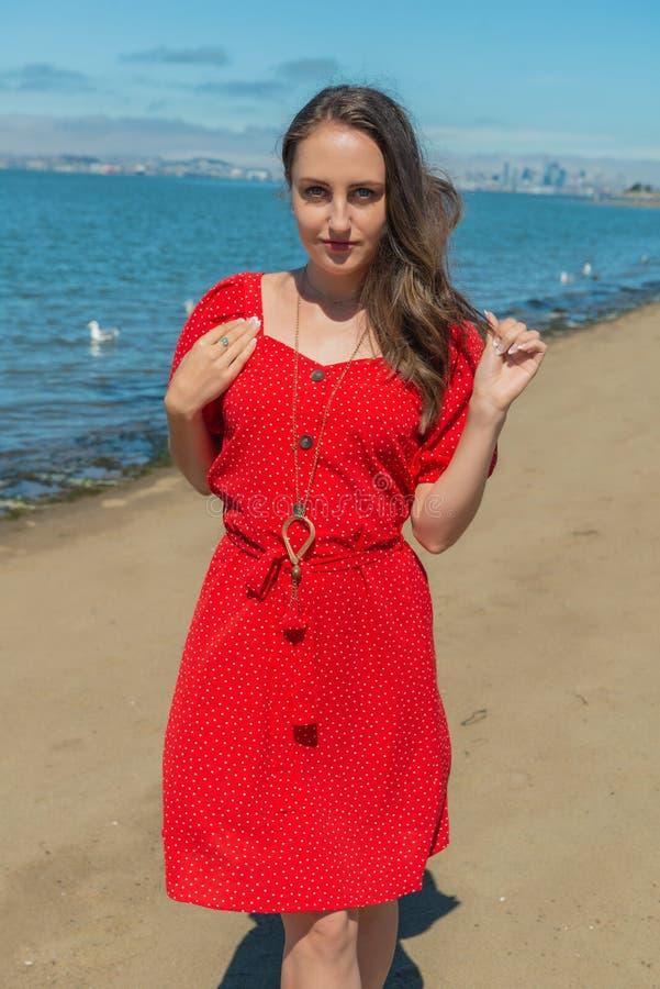Brunett i rött på en strand arkivbild