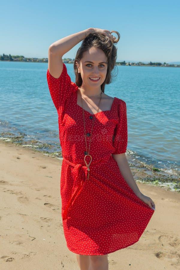 Brunett i rött på en strand royaltyfria bilder