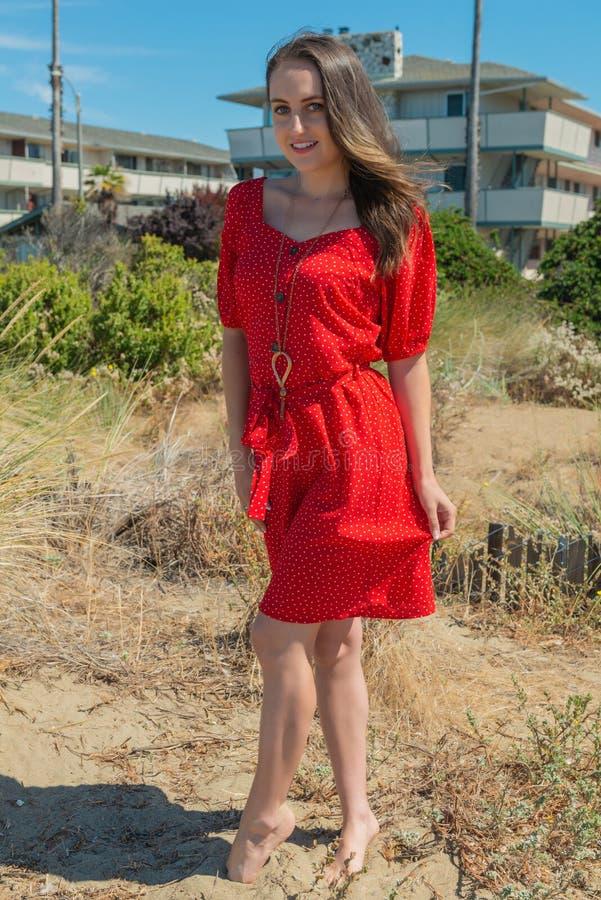 Brunett i rött på en strand arkivbilder