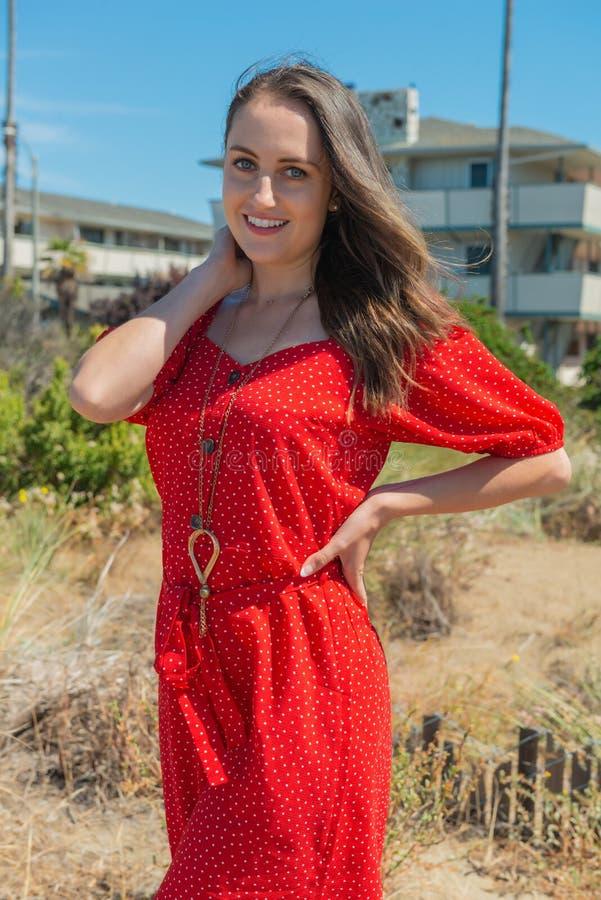 Brunett i rött på en strand royaltyfri bild