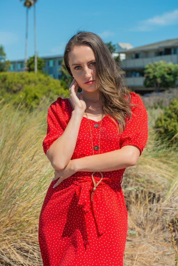 Brunett i rött på en strand arkivfoto
