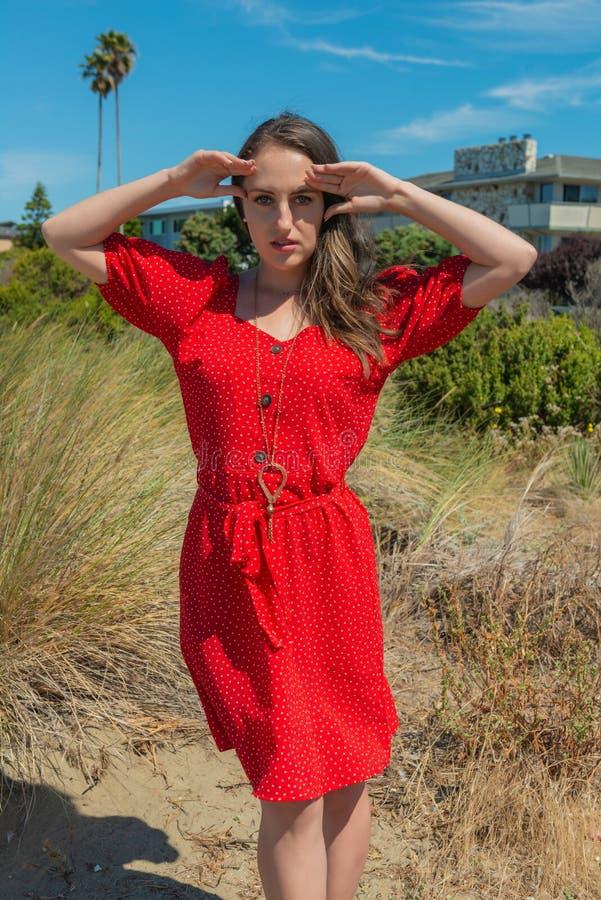 Brunett i rött på en strand fotografering för bildbyråer