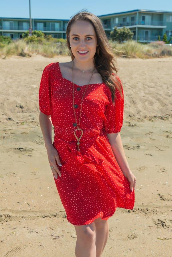Brunett i rött på en strand royaltyfri foto