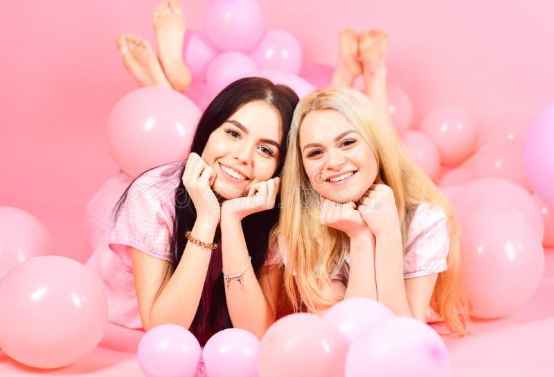 Brunett och blonda gulliga kvinnor i rosa pyjamas som poserar på kamera medan lekmanna- near luftballonger på slummerpartiet över royaltyfri bild