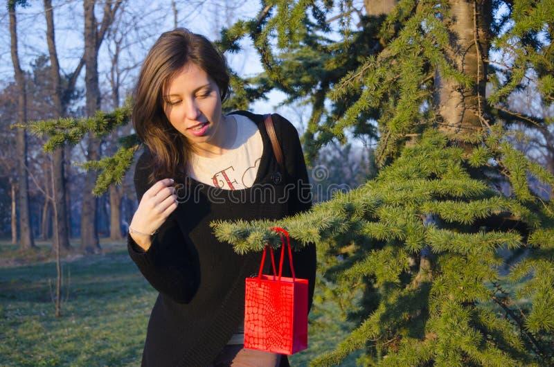 Brunett som finner hennes valentin gåva på ett träd arkivfoto