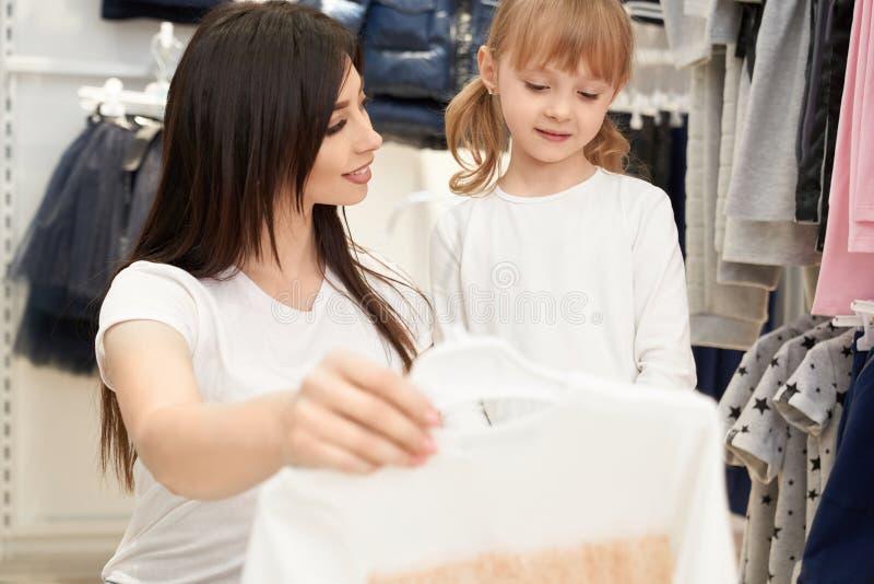 Brunett som håller den nya klänningen och ser dottern i lager arkivfoton