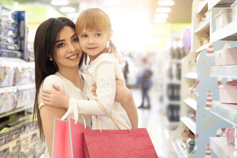 Brunett som h?ller barnet p? h?nder och shoppar i lager arkivbild