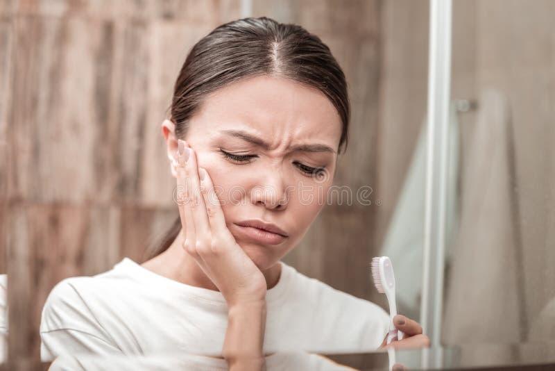 Brunett som har stark tandvärk, når att ha borstat dem royaltyfri bild