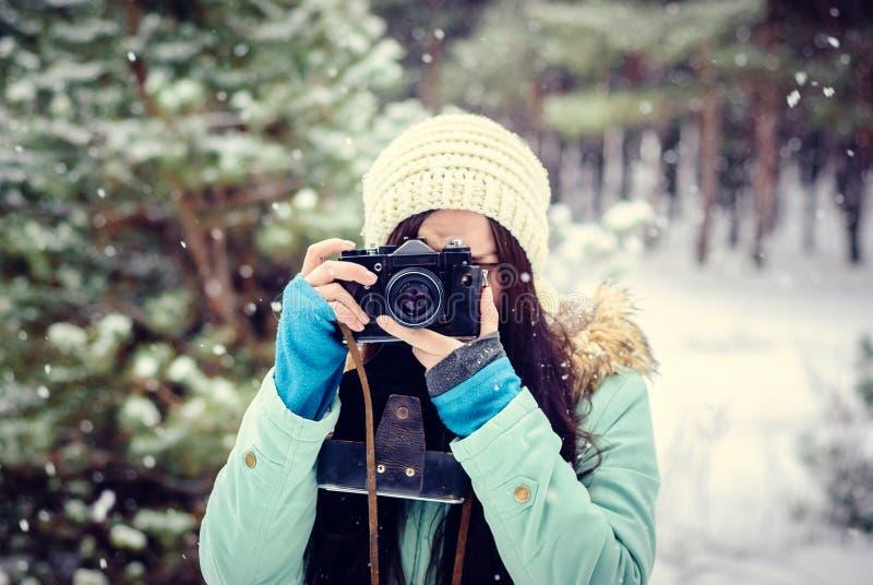 Brunett som ler flickan som fotograferas på en gammal tappningkamera i vinterskog arkivfoto