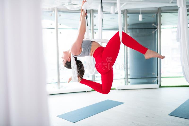 Brunett som str?cker hennes ben och g?r tillbaka flyg- yoga fotografering för bildbyråer