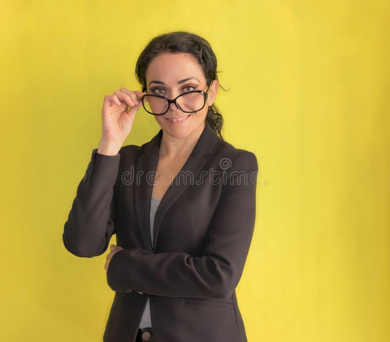 Brunettaffärskvinna som av tar hennes exponeringsglas och ler på kameran arkivfoto