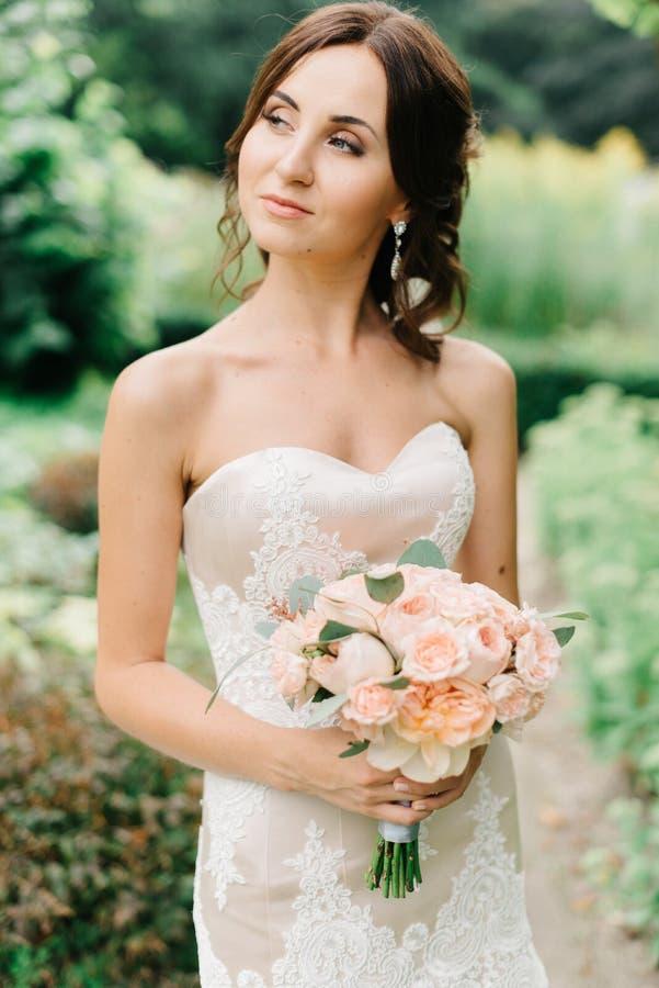 Brunettbruden ser bort rymma persikabuketten i henne armar arkivfoton