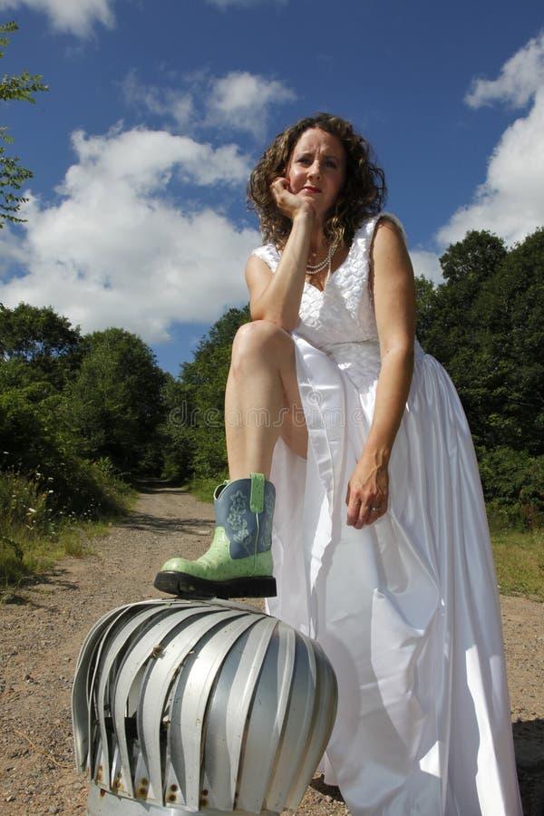 Brunettcowgirlbrud på en turbin utanför royaltyfria bilder