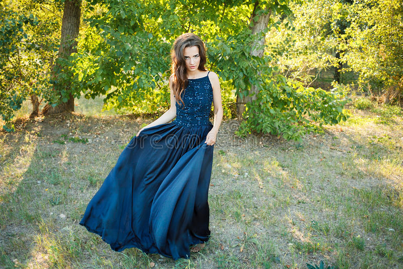 Brunettdans i en lång blåttklänning royaltyfri foto