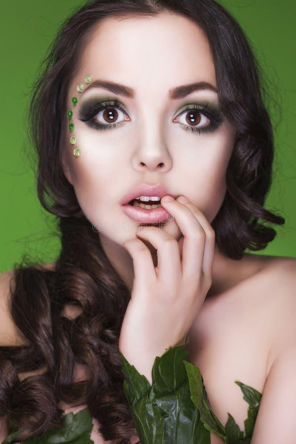 Brunettdryadkvinna med idérikt smink och pärlor på henne framsida, lockigt hår och dräkt som göras av sidor på grön backgro royaltyfri bild