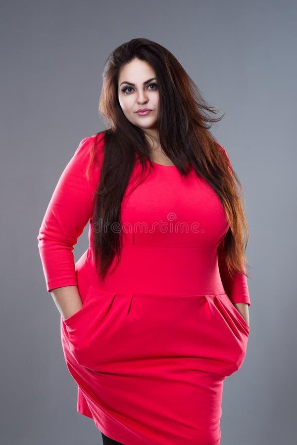 Brunette συν το πρότυπο μόδας μεγέθους στο κόκκινο φόρεμα, παχιά γυναίκα με μακρυμάλλη στο γκρίζο υπόβαθρο στοκ φωτογραφίες