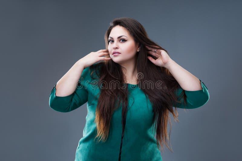 Brunette συν το πρότυπο μόδας μεγέθους στο πράσινο φόρεμα, παχιά γυναίκα με μακρυμάλλη στο γκρίζο υπόβαθρο στοκ εικόνες