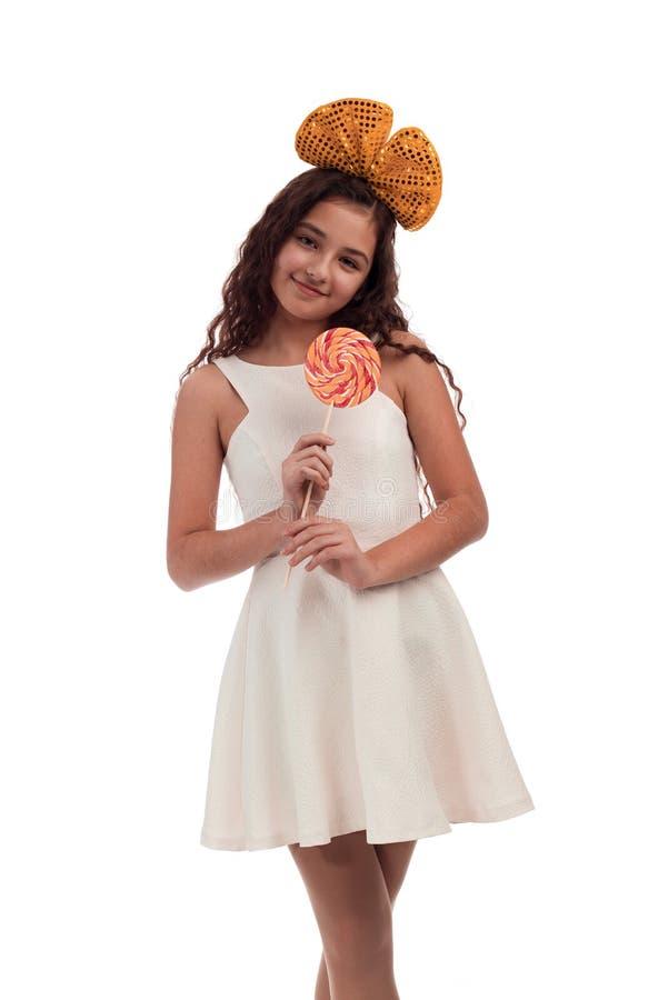brunette κοριτσιών με μακρυμάλλη σε ένα άσπρο φόρεμα με ένα τόξο στο κεφάλι της με μια μεγάλη καραμέλα σε ένα ραβδί στα χέρια που στοκ φωτογραφία