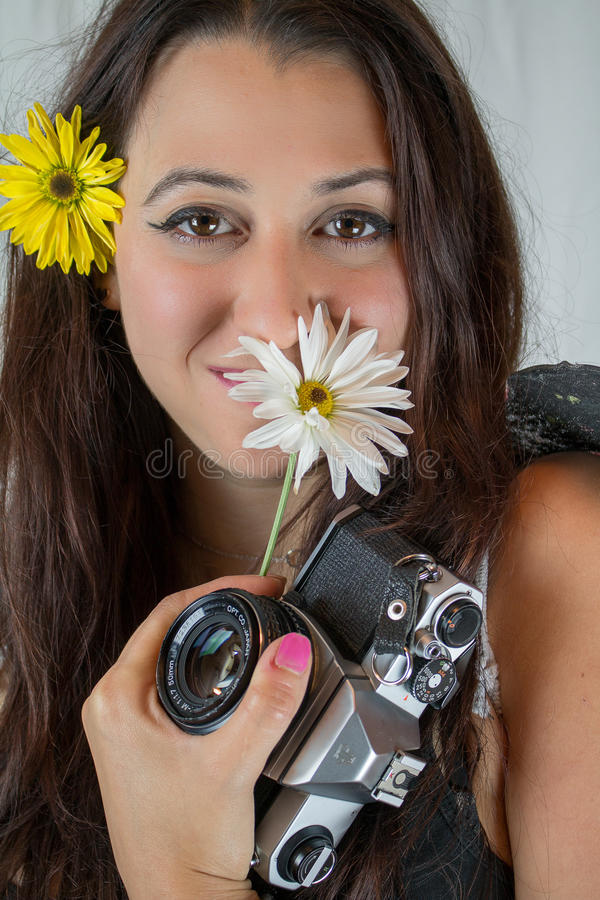 Brunette μεταξύ των λουλουδιών και της εκλεκτής ποιότητας κάμερας στοκ φωτογραφία με δικαίωμα ελεύθερης χρήσης