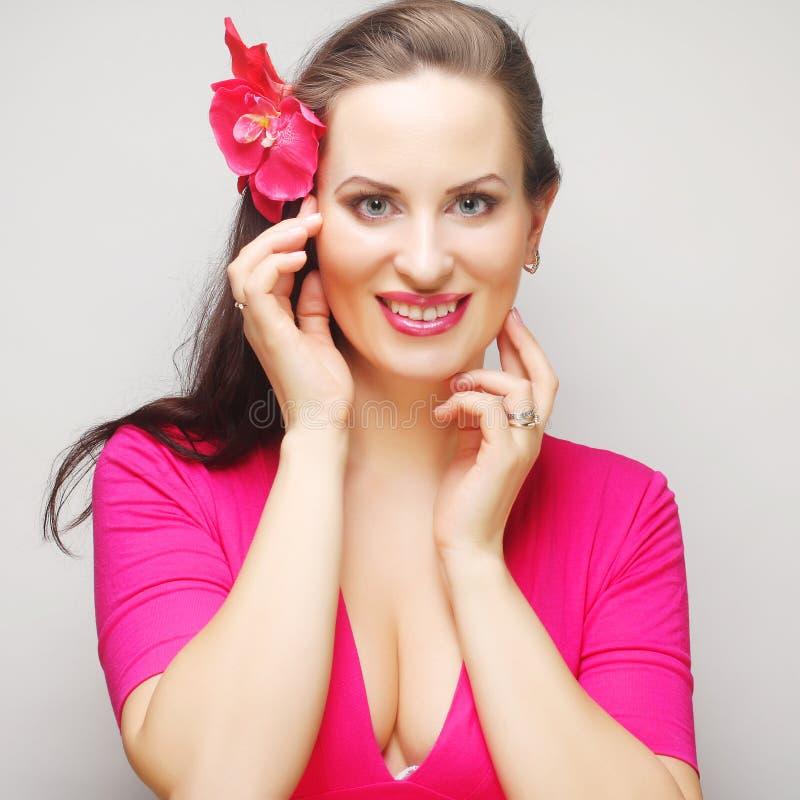Brunette με μακρυμάλλη στο ρόδινο ευτυχές χαμόγελο ένδυσης στοκ φωτογραφίες
