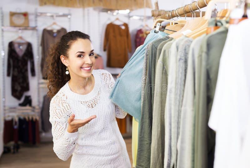Brunette που επιλέγει τη φούστα στο κατάστημα στοκ φωτογραφία