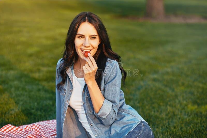 Brunette που τρώει τη φράουλα στο πάρκο στοκ εικόνες