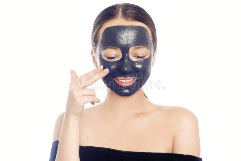 Brunette σε μια μαύρη μάσκα για το πρόσωπο Όμορφη φωτογραφία ενός κοριτσιού με το τέλειο δέρμα Ένα νέο κορίτσι φροντίζει για την στοκ φωτογραφίες με δικαίωμα ελεύθερης χρήσης