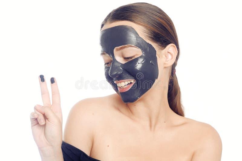 Brunette στη μαύρη μάσκα για το πρόσωπο Όμορφο κορίτσι με το τέλειο δέρμα Ένα νέο κορίτσι φροντίζεται Ένα κορίτσι παρουσιάζει μια στοκ εικόνες