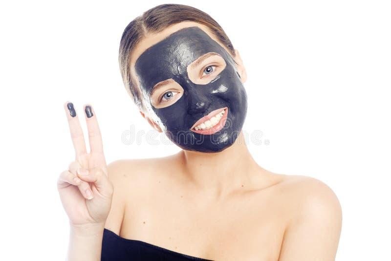 Brunette στη μαύρη μάσκα για το πρόσωπο Όμορφο κορίτσι με το τέλειο δέρμα Ένα νέο κορίτσι φροντίζεται Ένα κορίτσι παρουσιάζει μια στοκ φωτογραφίες
