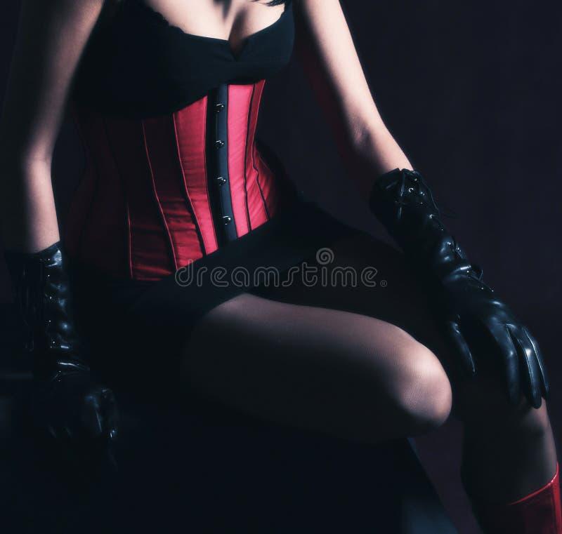 Brunette στον κόκκινο κορσέ πέρα από το μαύρο υπόβαθρο στοκ φωτογραφία με δικαίωμα ελεύθερης χρήσης