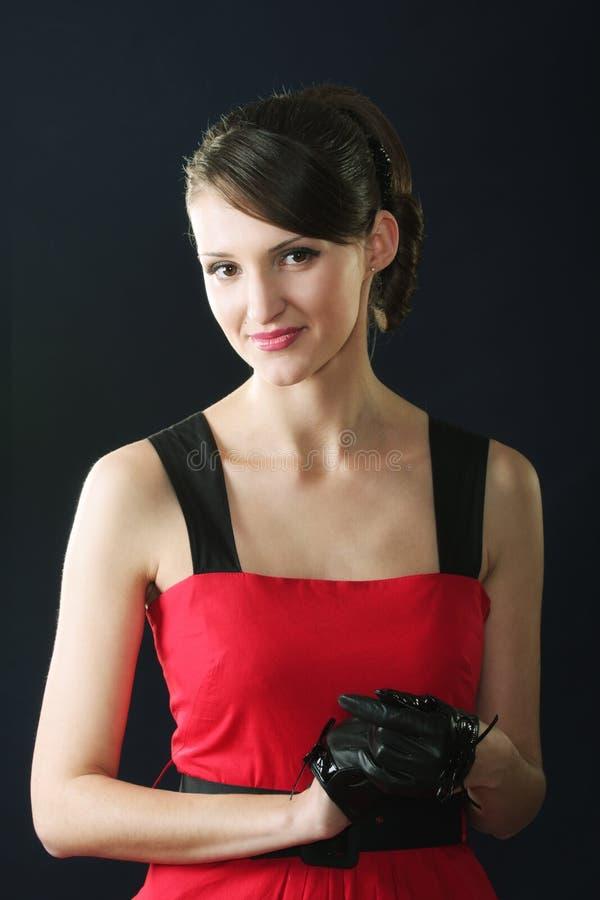 Brunette στο κόκκινα φόρεμα και τα γάντια στοκ φωτογραφία