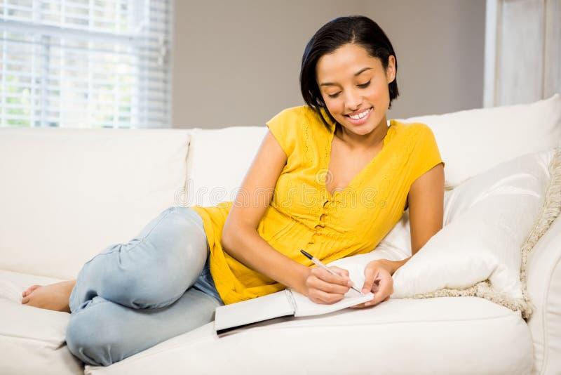 Brunette χαμόγελου που γράφει στο σημειωματάριο στοκ φωτογραφία με δικαίωμα ελεύθερης χρήσης