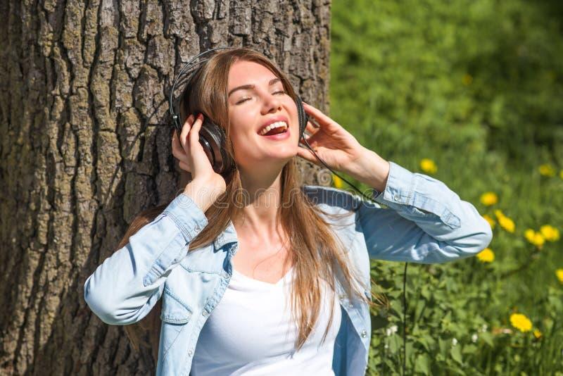Γυναίκα με τα ακουστικά στο πάρκο στοκ φωτογραφία με δικαίωμα ελεύθερης χρήσης