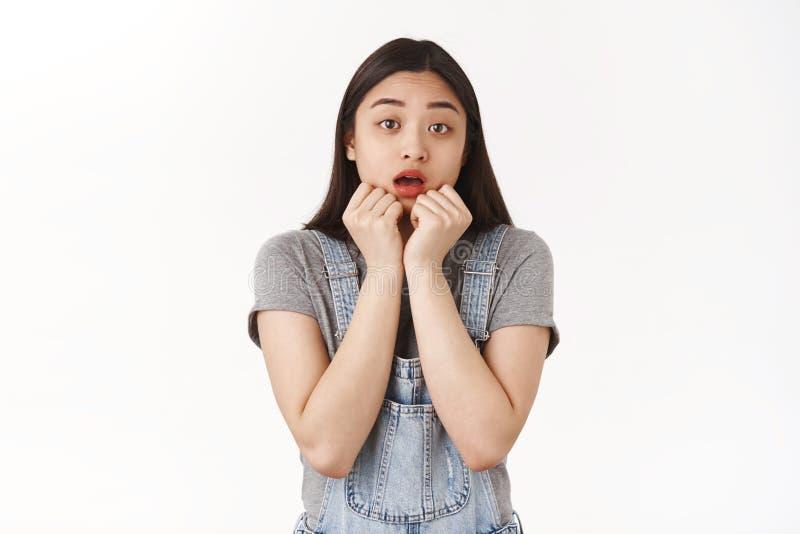 Brunette asian entusiasmada imagina se perguntando se a boca aberta suspirando intrigada de mãos perto dos lábios parece preocupa imagens de stock