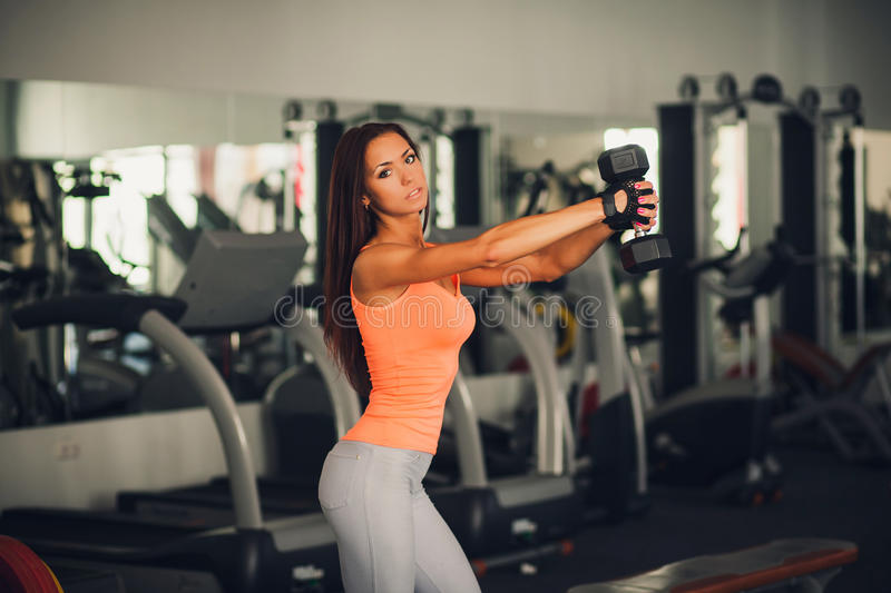 Brunette athlete lifts a dumbbell. In the gym. looking at the camera royalty free stock photography
