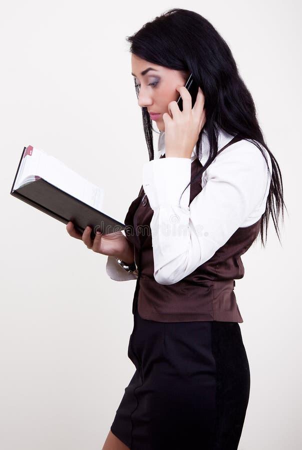 Brunette attirant avec le téléphone et l'agenda images stock