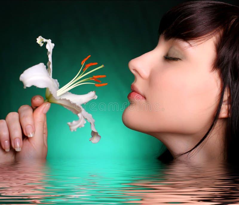 Brunette avec des fleurs de lis blanc dans l'eau photos libres de droits