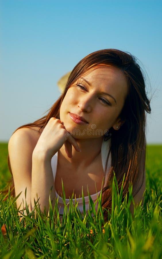Brunette avec du charme se trouvant sur l'herbe photos libres de droits