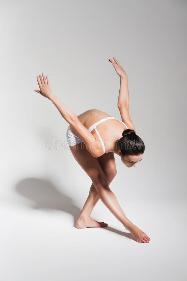 Brunette ballerina bending down to leg stock photos