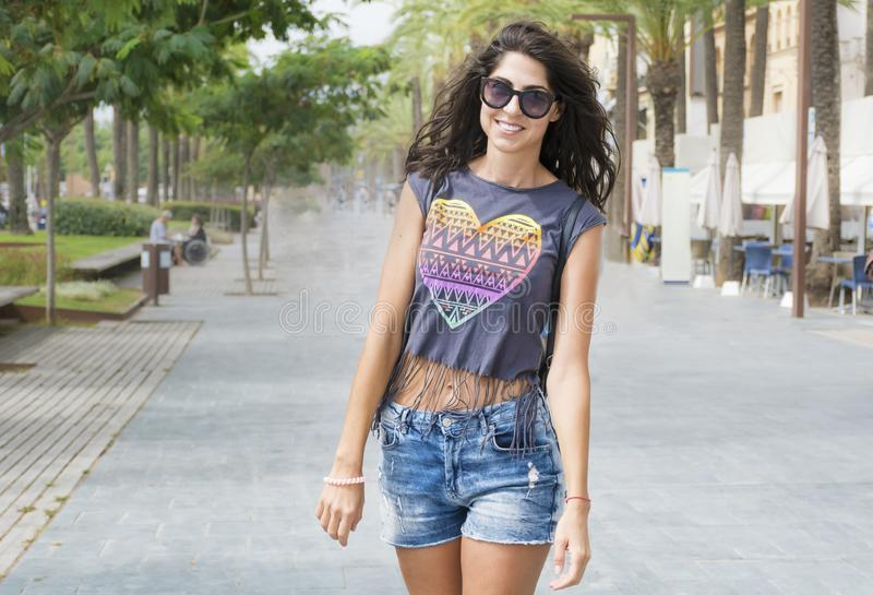 Young beautiful woman on the street. Brunette beautiful woman with denim shorts and casual shirt stock photography