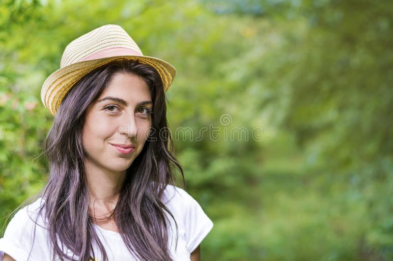 Young Beautiful Woman in a Green Park. Brunette beautiful woman with hat on a walk in a summer park stock image