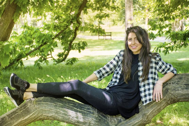 Young Beautiful Woman in a Green Park. Brunette beautiful woman on a walk in a summer park,sitting on a tree royalty free stock photos